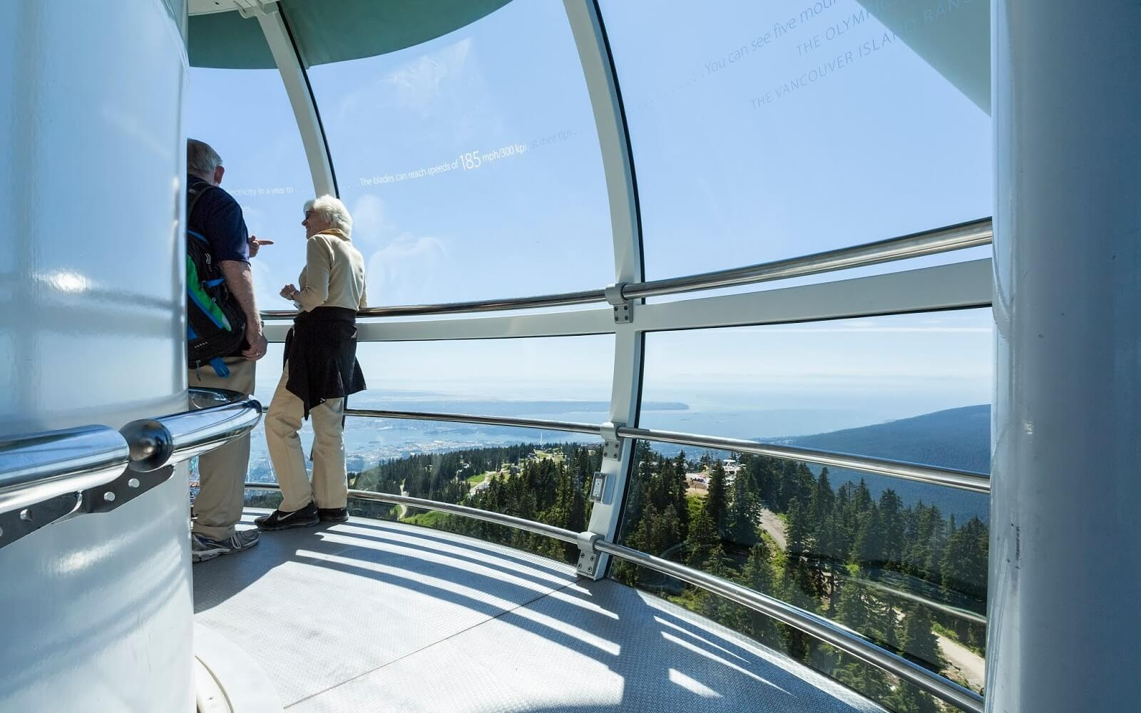 tourists look down on vancouver from the observatory at grouse mountain wind turbine