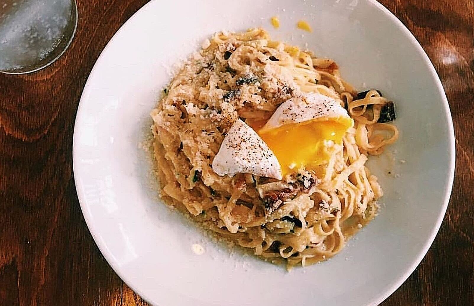 An egg drizzles over a plate of Tagliolini Carbonara