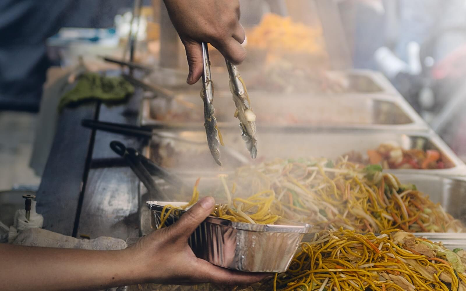 a woman serves noodles at the chinese night market in richmond bc