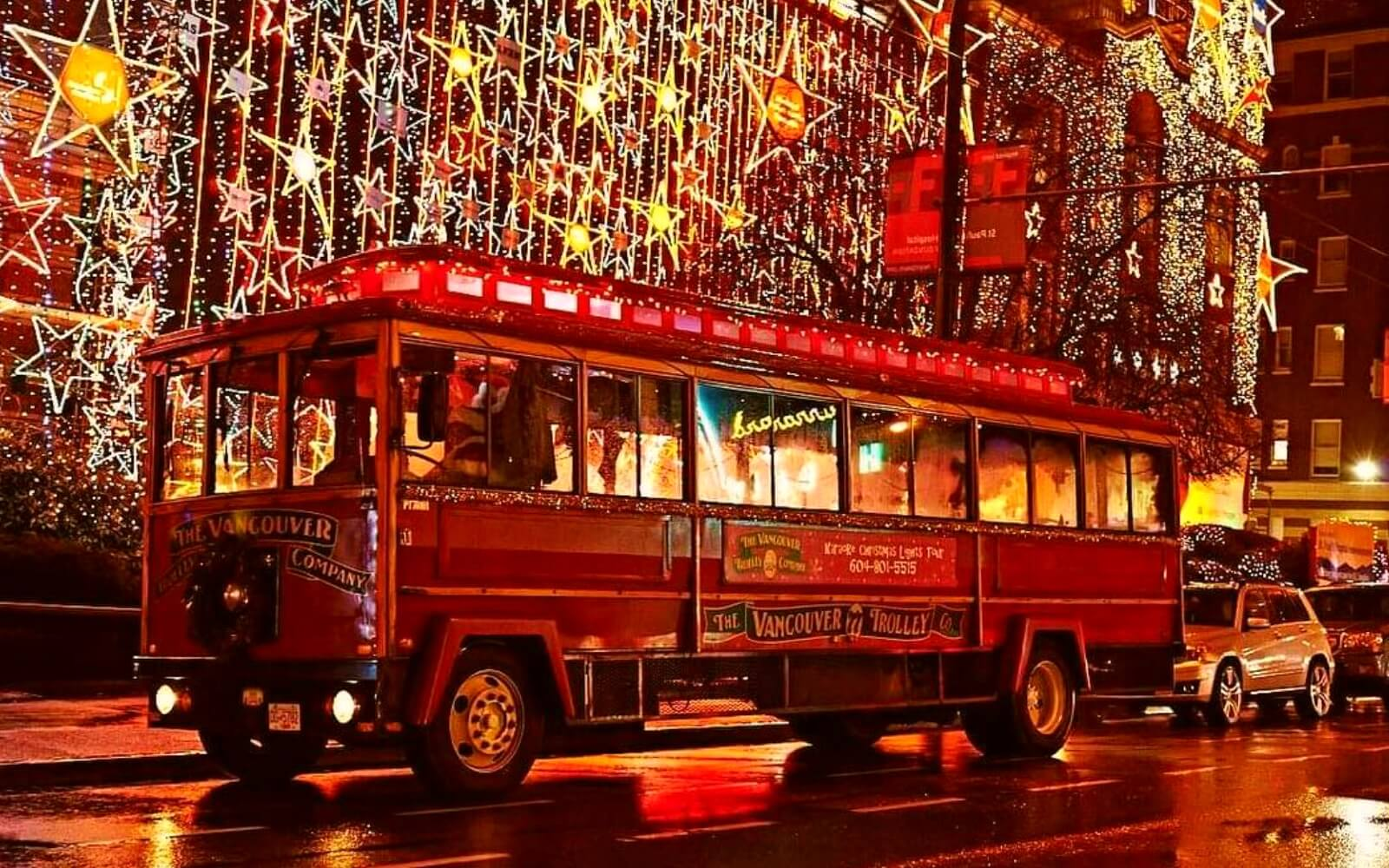 A Westcoast Sightseeing bus passes in front of Christmas lights