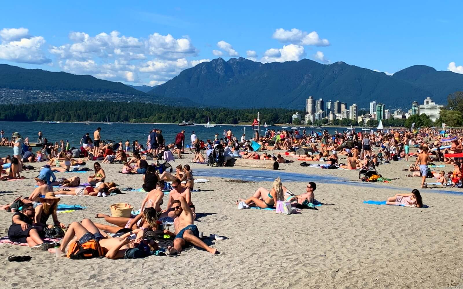 people suntanning at kits beach in vancouver with downtown and mountains